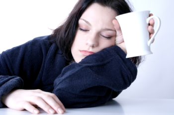 a woman with a coffee cup tries to wake up after a sleepless night